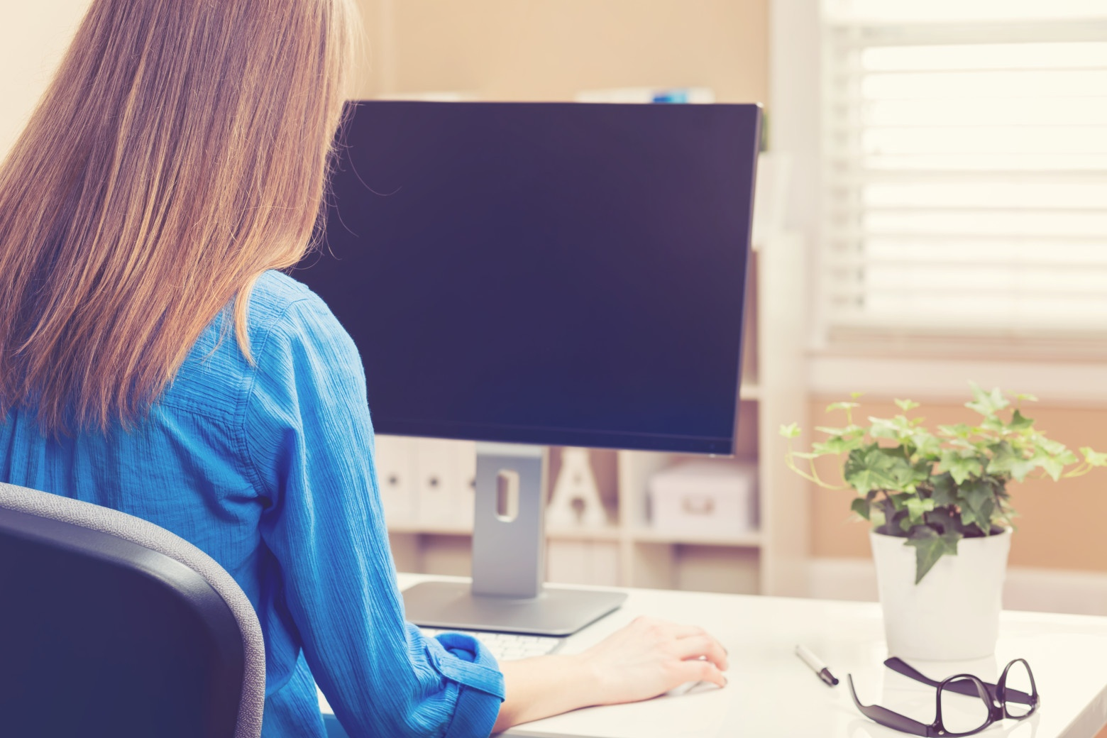 Looking over the shoulder of a young woman using her computer in her home office